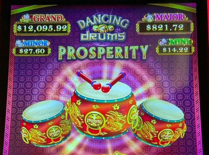 Dancing Drums Prosperity by Scientific Games logo and progressives
